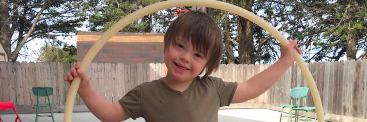 Boy standing in backyard with hula hoop