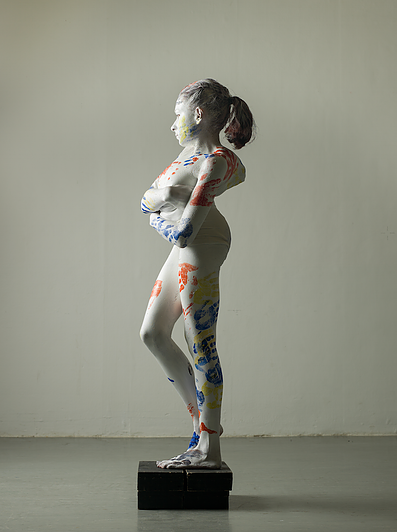 Rebecca Dann painted white standing like a statue.