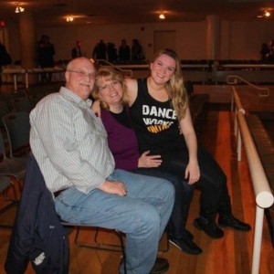 parents sitting with their daughter in an auditorium