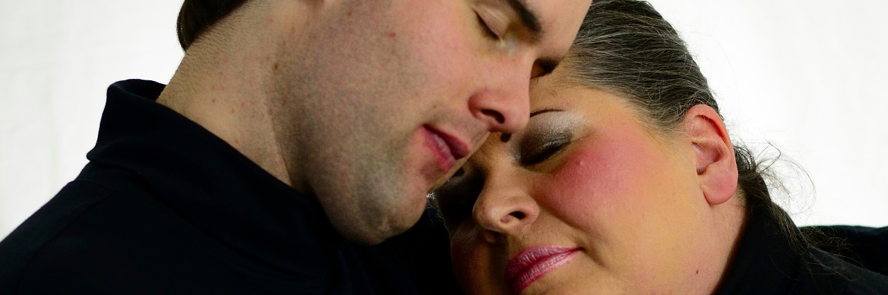 Man and woman holding hands, with woman head on man's shoulder, both of their eyes closed