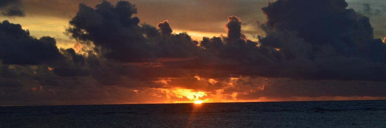 Sun breaking through dark clouds over water