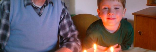 the author's dad and her young son sitting in front of a birthday cake with lit candles