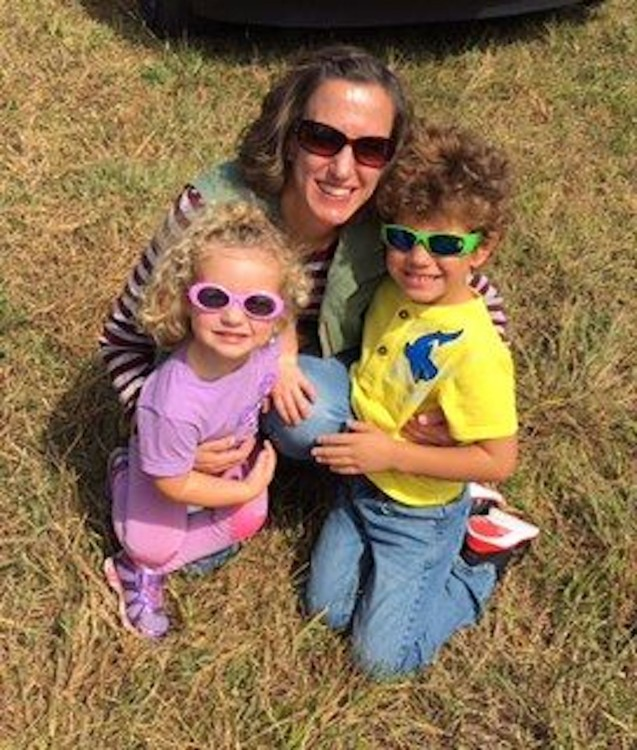 A mom and her two kids in sunglasses outside