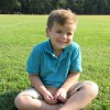 Boy in a blue polo shirt, sitting on the grass