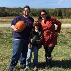 mom dad and son picking pumpkins