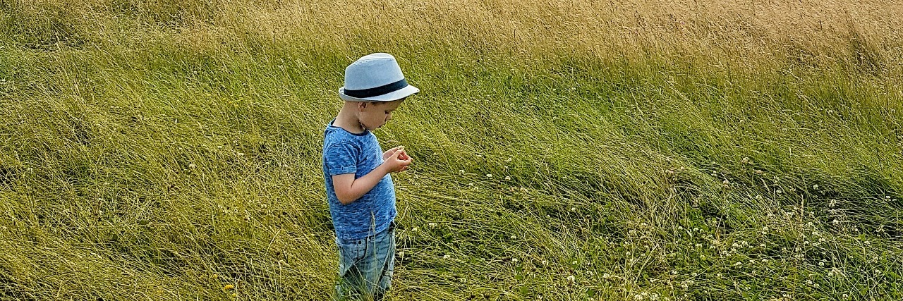 The author's son in a grassy field under a cloudy blue sky