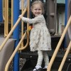 little girl playing on play structure at the park