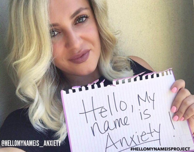 woman holding up a sign that reads: Hello, my name is anxiety.