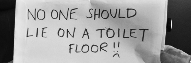 "Boy with sign saying ""No one should lie on a toilet floor!"""