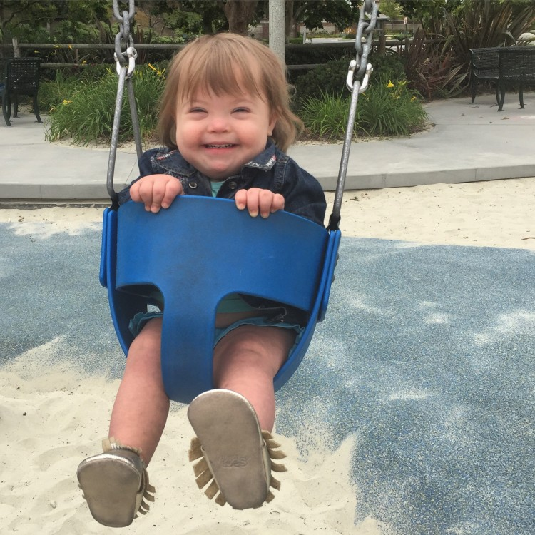 a little girl sitting in a baby swing and smiling