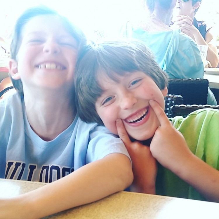 two kids smiling while sitting at table together