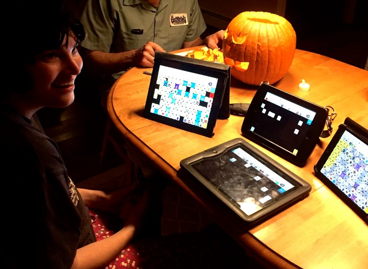 Jess with her AAC device at a table
