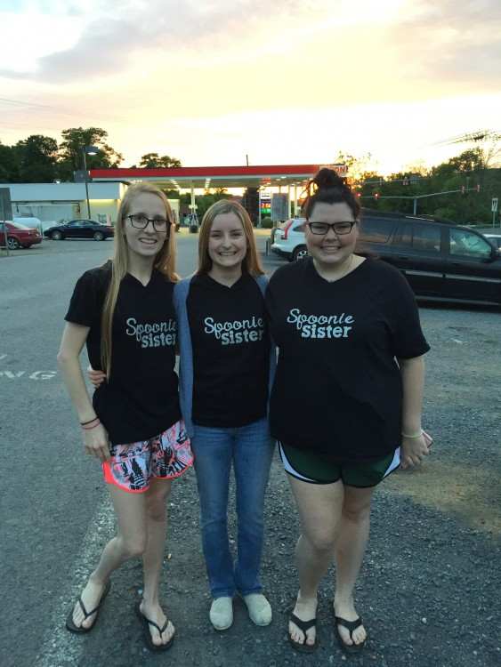 three girls standing in parking lot at sunset
