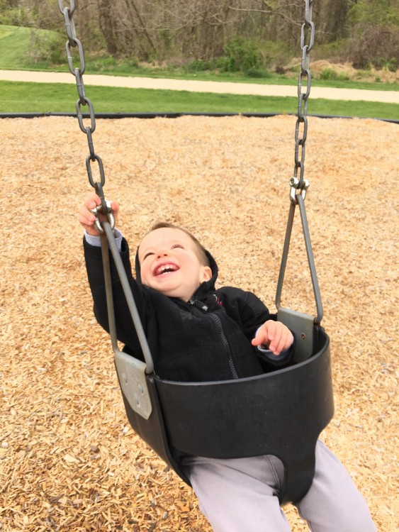 boy sitting in baby swing at park