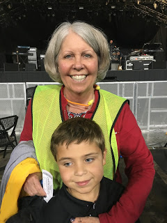 female security guard posing with young boy at concert