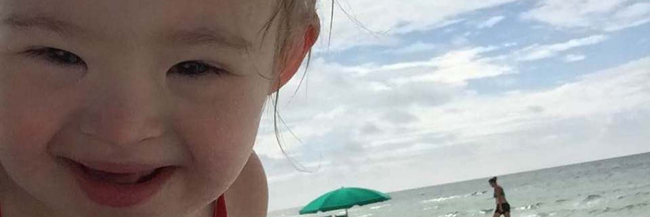 Baby girl on the sand at the beach