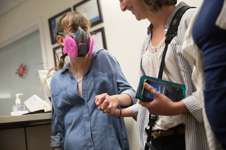 girl wearing breathing mask and holding woman's hand