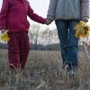 Mother and daughter holding hands in field