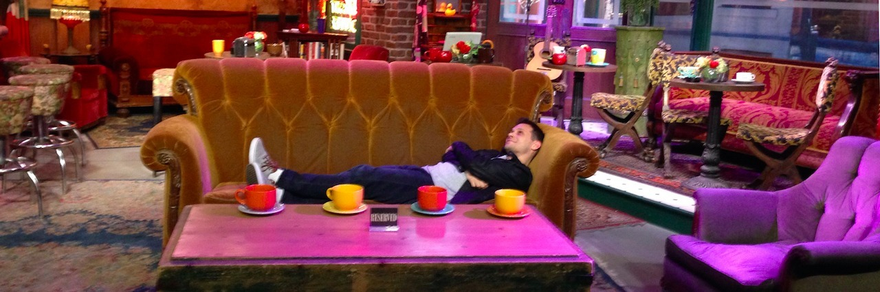 "A man laying on a couch from the set of ""Friends"""