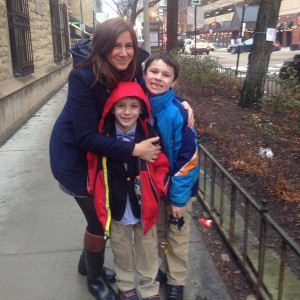 mother hugging two sons while on the sidewalk