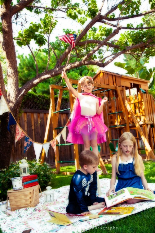 Young girl wearing a fairy costume outside with two other children
