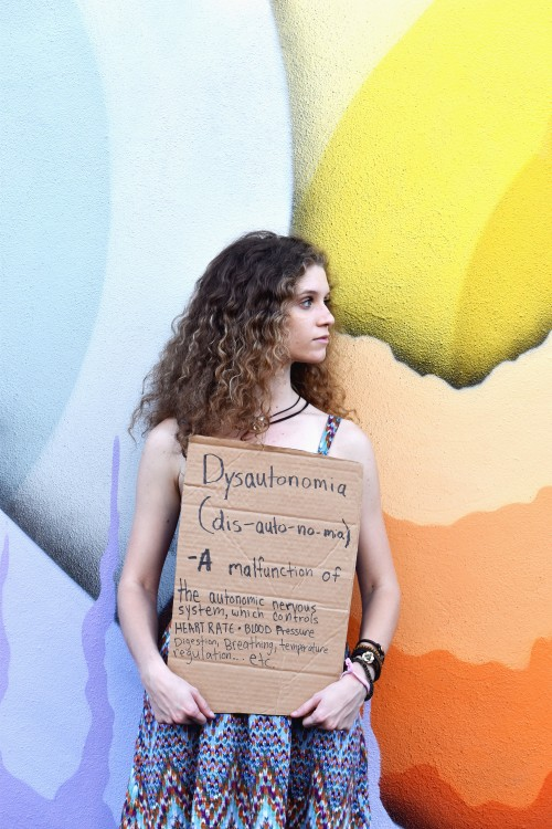 a woman holds a sign that says dysautonomia (dys-auto-no-mia) a malfunction of the autonomic nervous system, which controls heart rate, blood pressure, digestion, breathing, temperature, regulation, etc...""