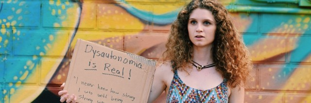 a woman holds a sign that says dysautonomia is real! i never knew how strong i was until being strong as my only choice