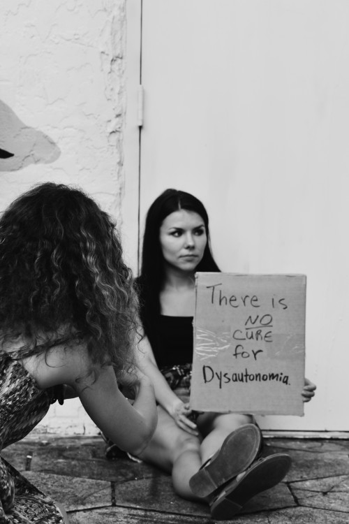 a woman sits on the ground getting her photo taken holding sign that says there is no cure for dysautonomia