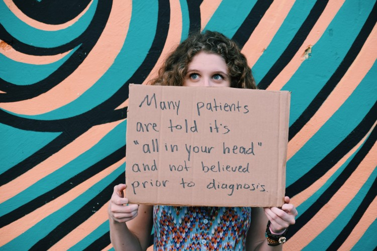 woman holds a sign that says many patients are told it's all in your head and not believed prior to diagnosis