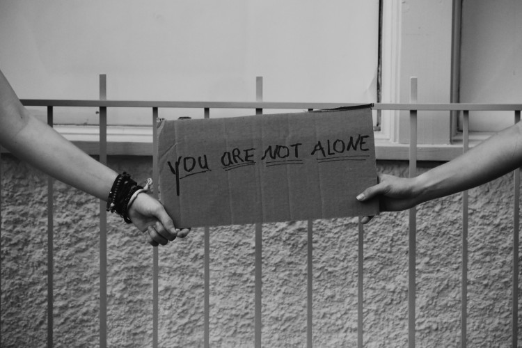 two hands hold a sign that says you are not alone