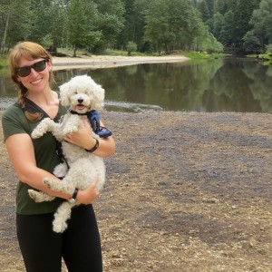 Jen Pearlstein at Yosemite National Park with her cervice dog, a white poodle.