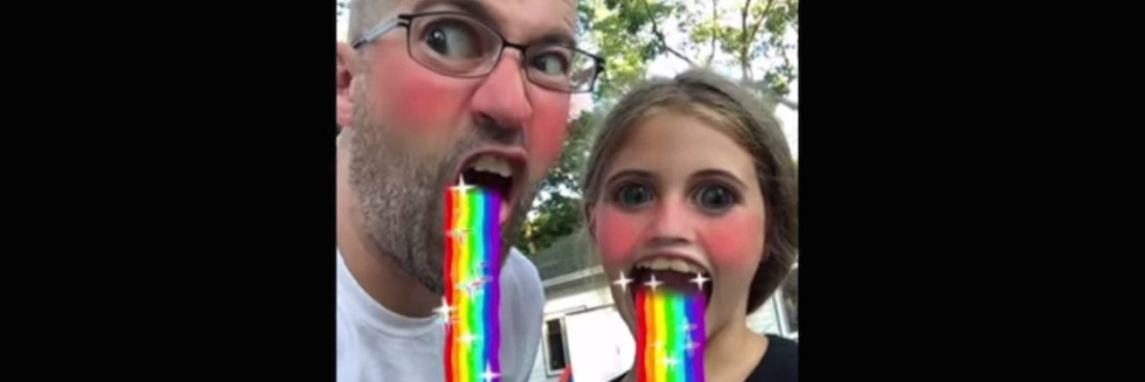A man and his daughter using a rainbow throw up Snapchat filter.