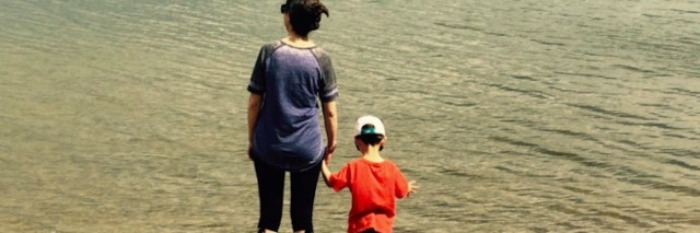 A woman and child holding hands, standing at the shore