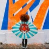Girl standing in front of wall wearing cape with tiger on it