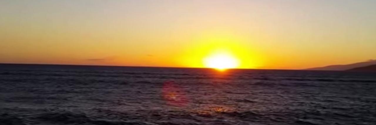 the sun setting behind the ocean