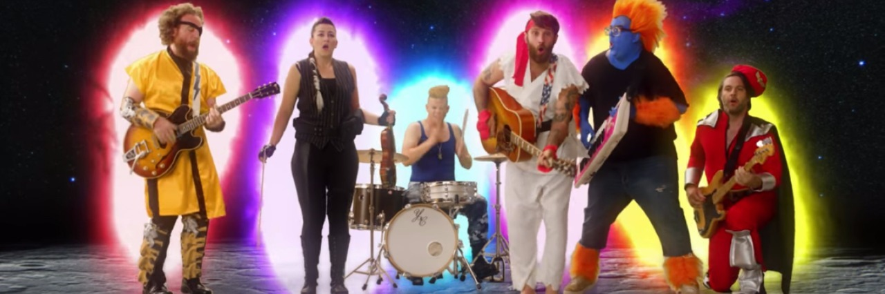 Still from a Strumbrella's music video. Band is dressed in costumes and playing in outer space.