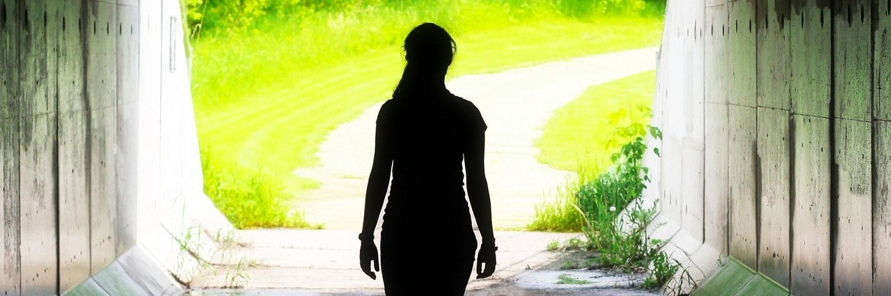 woman walking towards the light at the end of a tunnel