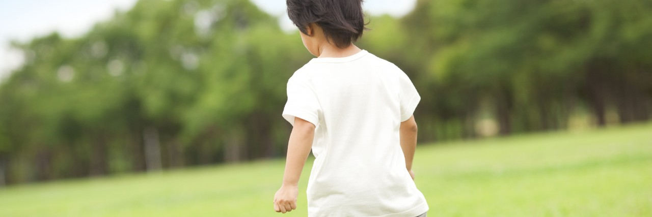 Boy running through field.