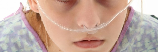 Ill american 16 year old girl in hospital gown with oxygen tube over white background.