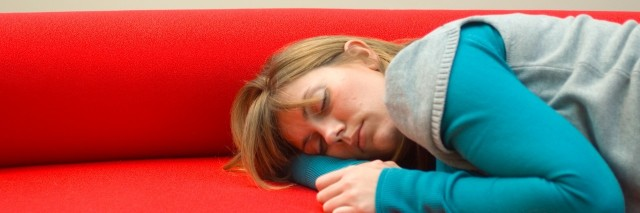 woman sleeping on red couch