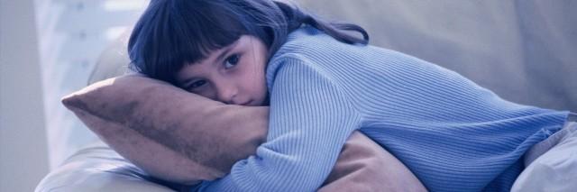 young girl hugging cushion while laying on sofa