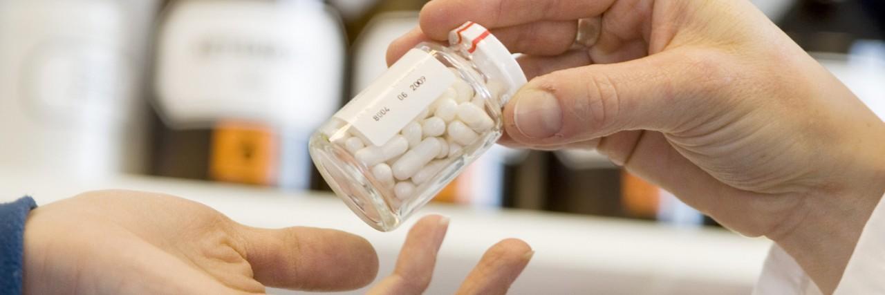 Pharmacist giving pill bottle to customer