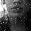 woman looking out a window with raindrops