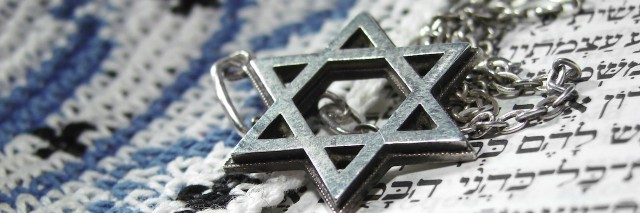 Jewish Star of David necklace laying on a paper with Hebrew letters