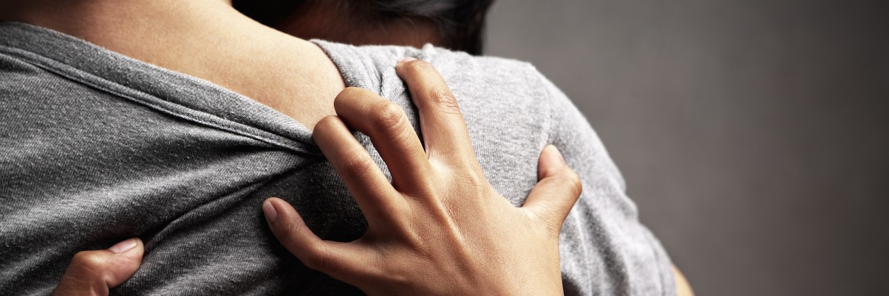 a woman hugging a friend, grabbing back