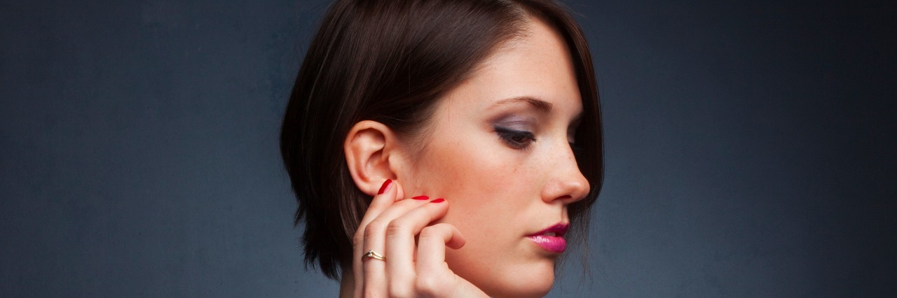Profile of woman with hand near her ear