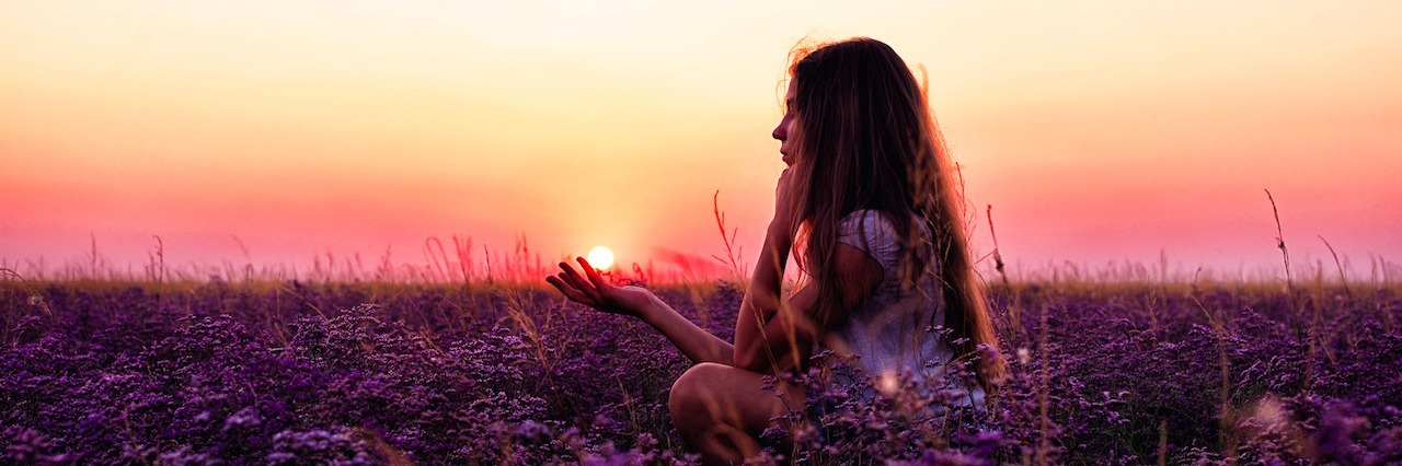 girl in a field of flowers at sunset