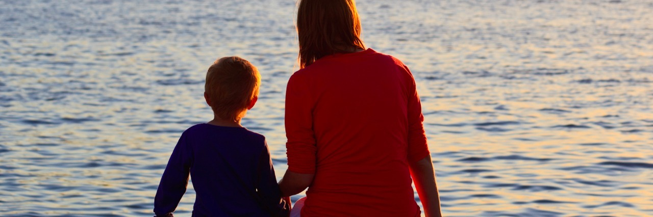 Mom and son sitting near water, looking at sunset landscape