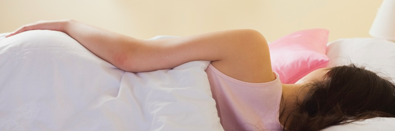 woman in bed sleeping, rear view