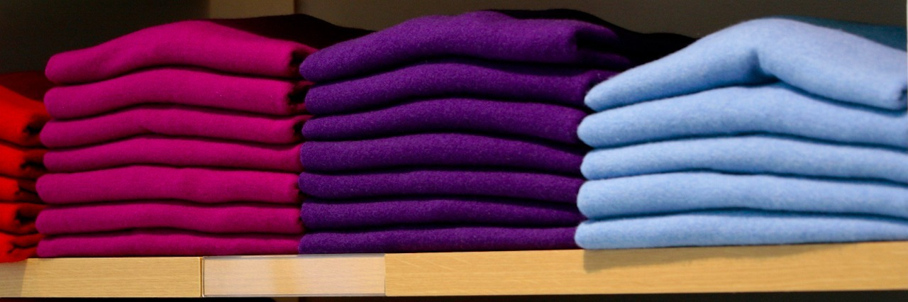 Colorful sweaters folded on shelves in clothing store